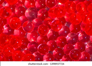 Transparent red hydrogel balls. Red water gel balls with bokeh. Polymer gel Silica gel. Liquid crystal ball with reflection. Red balls texture background