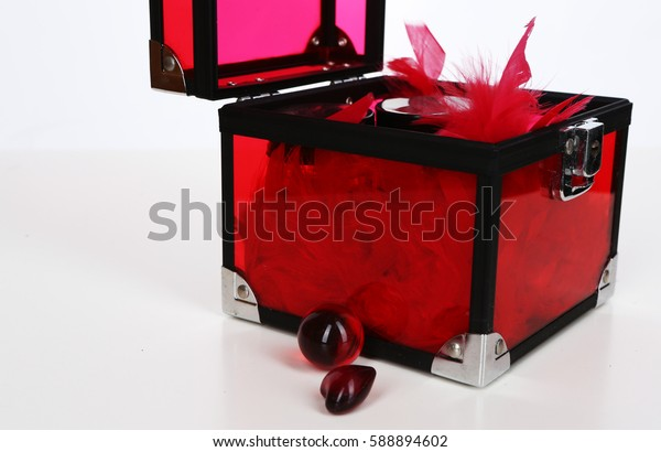 Transparent red plastic box full of ostrich feathers