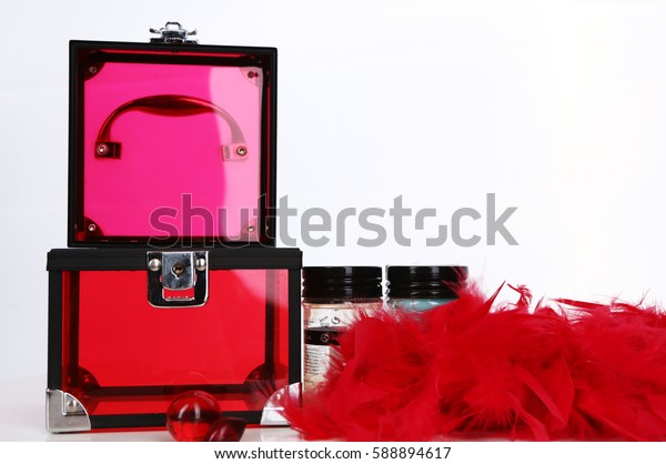 Transparent red plastic box with ostrich feathers