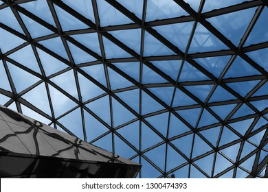 Transparent roof of hi-tech building. Abstract modern architecture photo of industrial or office building with glazed supporting structure of ceiling. Miminal interior design with geometric pattern.