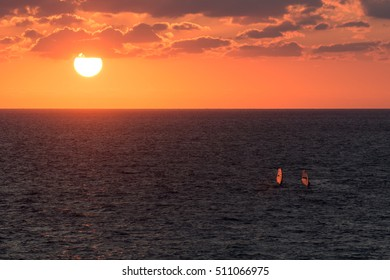 Transparent sails of wind-surfers lit orange by the backlight of the sunset