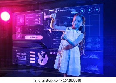 Transparent screen. Clever progressive girl smiling and feeling confident while standing in front of a transparent holographic screen and putting her hands on it