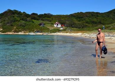 Transparent sea, sandy beach, tourist. Furugelma Island. Primorye. Russia.