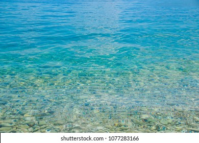 Transparent shallow water with rocky bottom, fading away to deeper area at top.Crystal clear water with transparent surface shine under the bright summer sun. Colorful underwater stones.