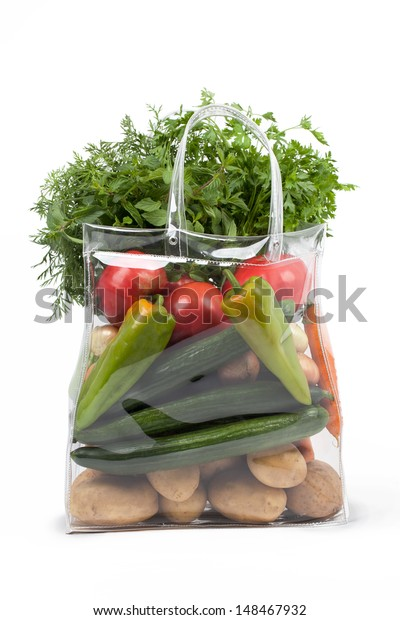 Transparent shopping bag with different fresh vegetables.