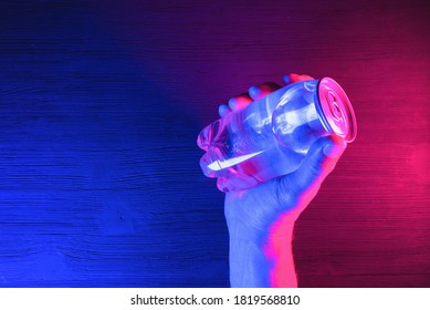 A transparent soda can in the neon lights on the black table background.