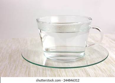 transparent tea cup with hot water on table cloth