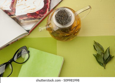 Transparent teapot with green tea with book and glasses on a green tablecloth