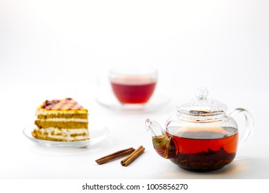 Transparent teapot with tea, glass cup and cake on white background
