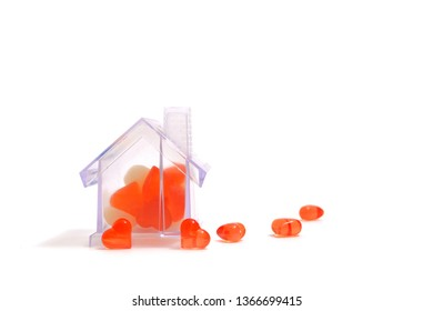 Transparent toy house, toy-filled hearts. Next to the house of the heart. The concept of building with love.