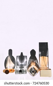 Transparent unisex perfume bottles in different sizes and shapes on white background with strong shadows.