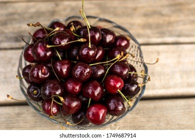A transparent vase with cherries stands on a wooden bench. - Shutterstock ID 1749687914