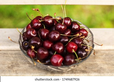 A transparent vase with cherries stands on a wooden bench. - Shutterstock ID 1749687926