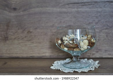 Transparent vase with white, beige and brown dry flowers, on a wooden background, aromatherapy.