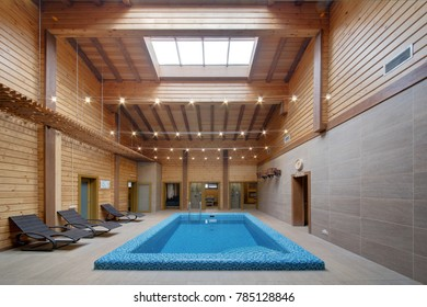 Transparent water in the pool in the building of a sauna with high wooden ceilings