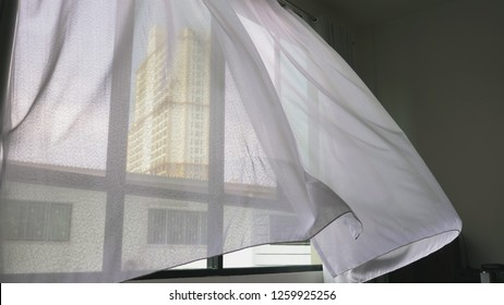 Transparent window curtain, gently moved by the wind. outside the window you can see the skyscrapers