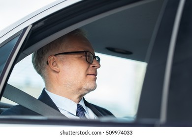 transport, business trip and people concept - senior businessman driving on car back seat
