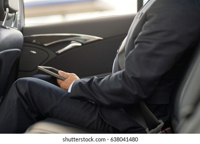 transport, business trip, technology and people concept - senior businessman with tablet pc computer driving on car back seat
