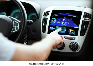 transport, destination, modern technology and people concept - male hand searching for route using navigation system on car dashboard screen