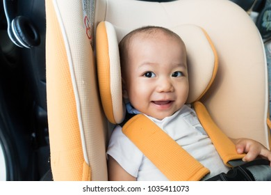 Transport, safety, childhood road trip and people concept - happy infant baby boy sitting in baby car seat,Child in auto baby seat in car.