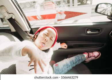 Transport, safety, childhood road trip and people concept - happy little girl sitting in car, Child in auto car and smile.Adorable little girl looking camera.