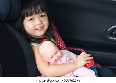 Transport, safety, childhood road trip and people concept - happy little girl sitting in baby car seat, Child in auto baby seat in car, Adorable little girl in the car.