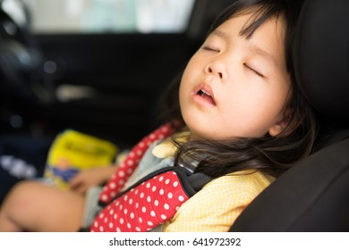 Transport, safety, childhood road trip and people concept - happy little girl sleeping in baby car seat, Child in auto baby seat in car, Adorable little girl in the car.