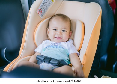Transport, safety, childhood road trip and people concept - happy infant boy sitting in baby car seat, Child in auto baby seat in car, Asian boy in Christmas vacation.