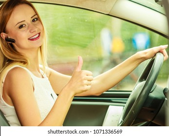 Transport and safety concept. Young blonde woman driving car using her mobile phone and headset, giving thumb up
