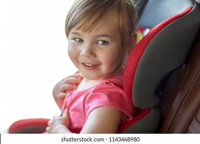 transport, safety, road trip and childhood concept - close up of happy little girl sitting in baby car seat