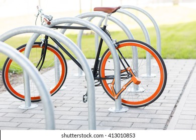 transport, storage, security and safety concept - close up of fixed gear bicycle locked at street parking outdoors