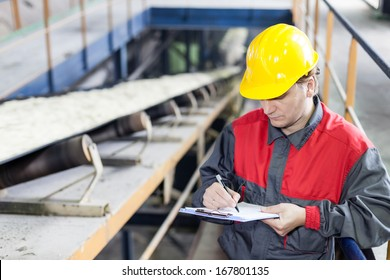 Transport of sugar on the production line , worker writes on the paper