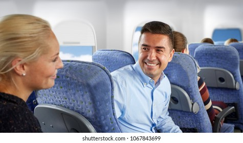 transport, tourism and air flights concept - happy passengers or tourists talking in plane over porthole background