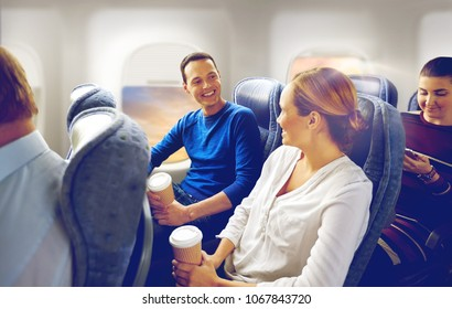 transport, tourism and air flights concept - happy passengers or tourists with coffee talking in plane over porthole background