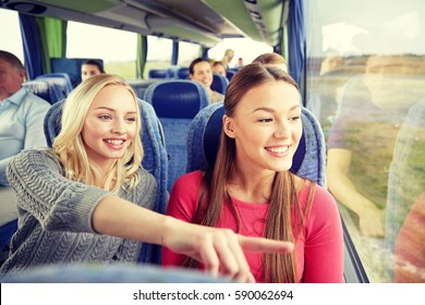 transport, tourism, friendship, road trip and people concept - young women or teenage friends riding in travel bus