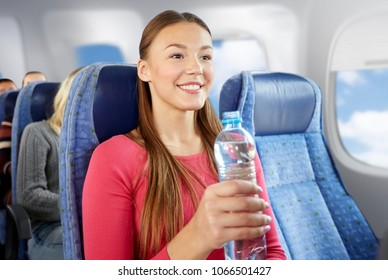transport, tourism and people concept - happy young woman with water bottle in plane over porthole background