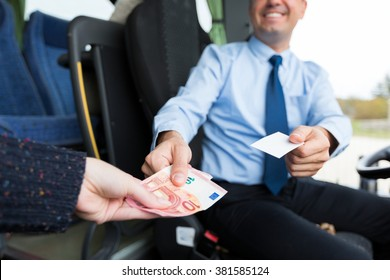 transport, tourism, road trip and people concept - close up of bus driver selling ticket to passenger