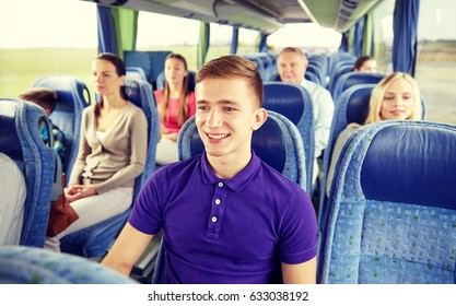 transport, tourism, road trip and people concept - happy young man sitting in travel bus or train