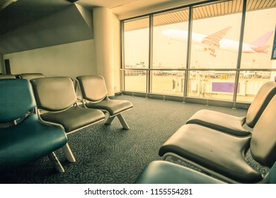 transport and travel concept. passenger seat in Departure. airplane flying past departures lounge window, view from airport terminal.sun light in vintage color selective focus,