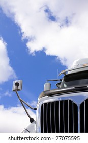 Transport truck against sky with clouds