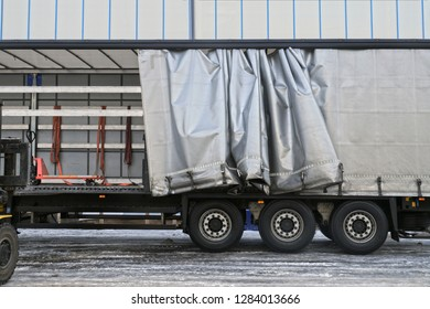 Transport and unloading. A semi-trailer with an exposed tarpaulin during unloading.