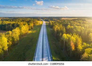 Transportation background. Free road to horizon. Aerial autumn landscape with blue sky and sunny forest. High way with new cover.
