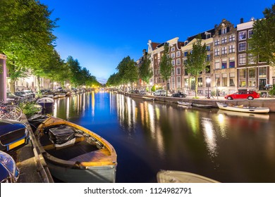 Transportation of boat, car, bicycle and apartment, house, along Amsterdam canal with reflection of light and star from blue sky at night in summer at Amsterdam the popular city of Netherlands