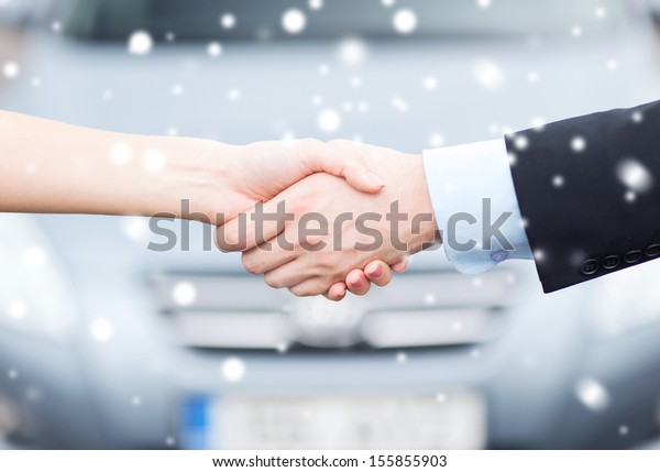 transportation, business, shopping and ownership concept - customer and salesman shaking hands outside