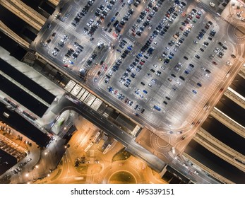 Transportation, cars on big parking at night. Aerial view in Krakow, Poland. Railway station and auto-bus station