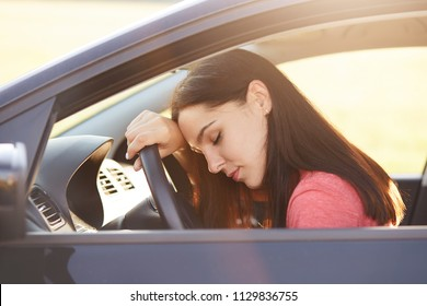 Transportation concept. Tired beautiful woman driver has sleepy expression, stop on road as can`t drive any more, wants to have rest, leans at wheel, poses in car, feels overworked and fatigue