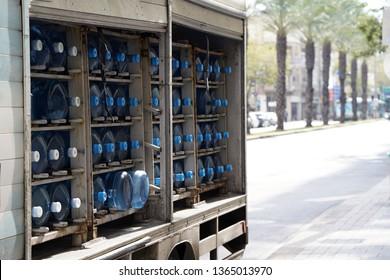 Transportation of drinking water bottles. van transports a full load of blue large drinking water bottles. Car body with potable water bottles. Stacked plastic bottles.