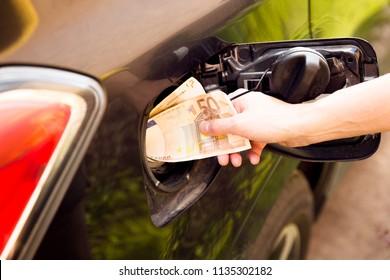 Transportation expenses concept - Euro money in car fuel tank