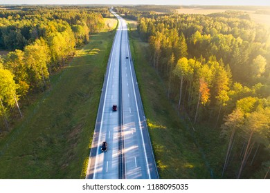 Transportation. Highway aerial view. New highway with cars view from above. Road in forest in the evening. Autumn landscape with road and sunlight.