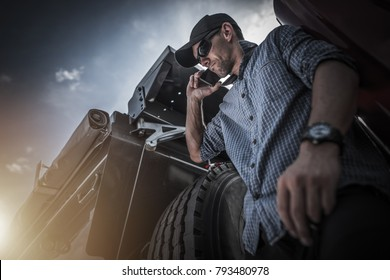 Transportation Industry Business. Caucasian Semi Truck Driver in His 30s Talking with Client Over the Phone While Seating on His Truck. Business Phone Call.